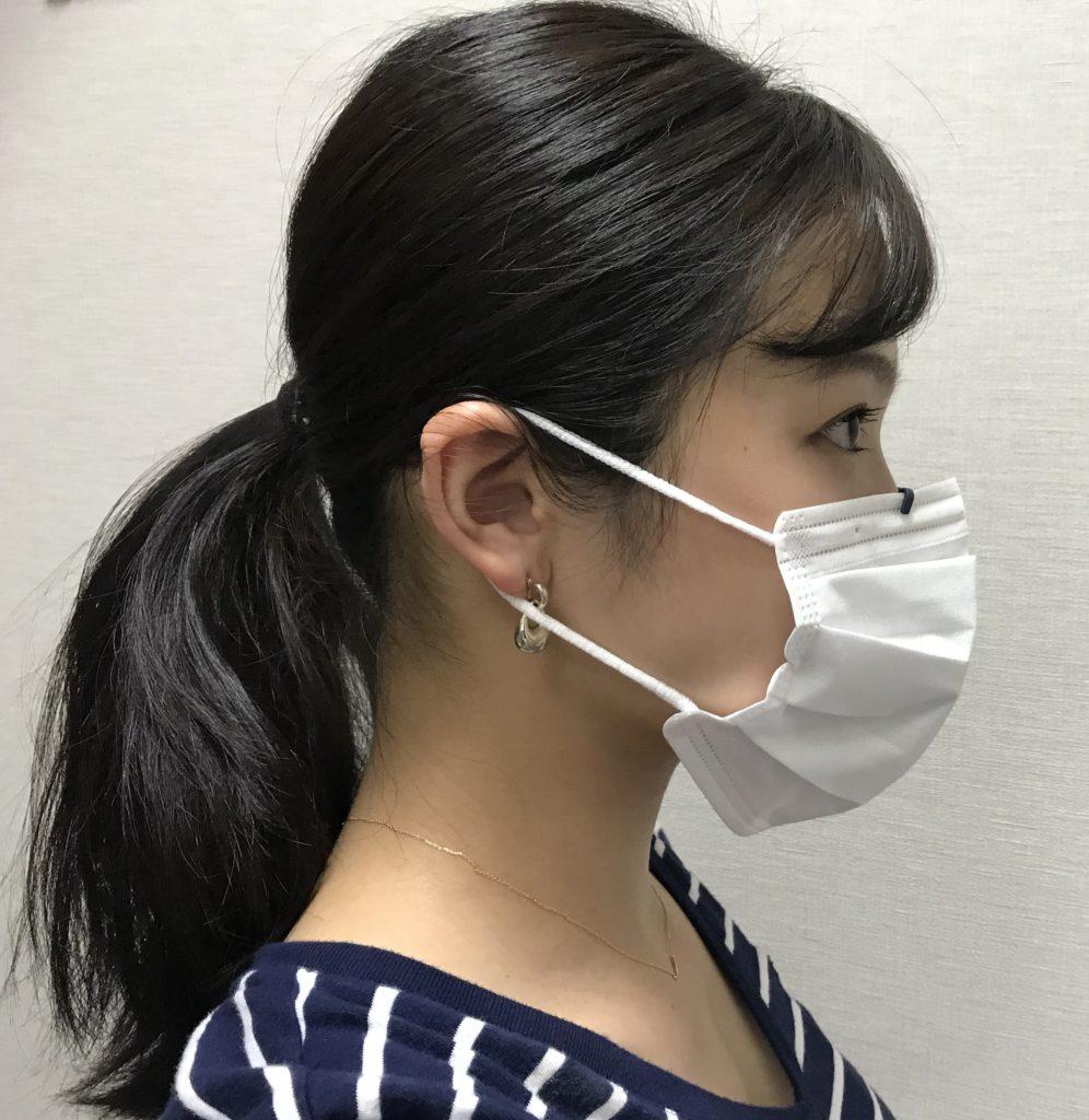 Musha_Kuchimoto」を付けたマスクを着用する女性